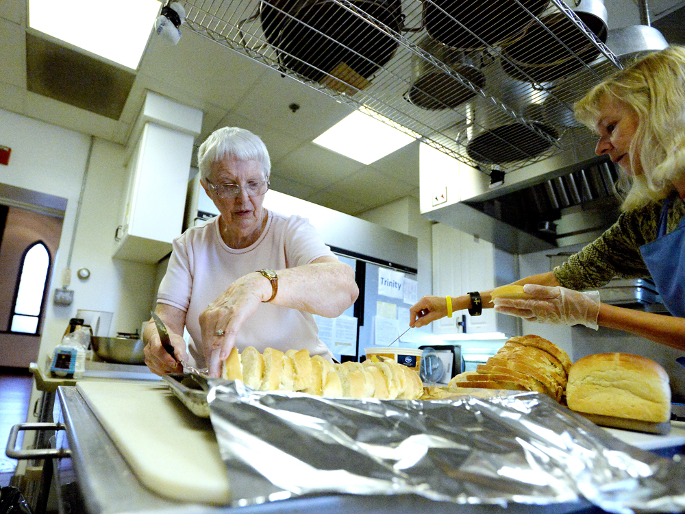 Phyllis Bolton of Covenant Presbyterian Church helps Pat Clark of Trinity Episcopal Church with slicing up bread in preparation for Noon Lunch at Trinity in Staunton on Wednesday, Nov. 12, 2014.