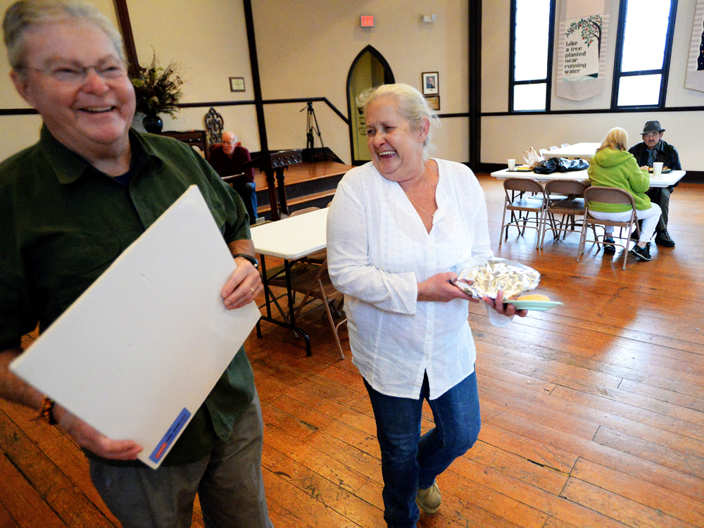 "Janet Wood, aka. ""Queen,"" shares a laugh with one of the volunteers as she carries a lunch for her brother during Noon Lunch at Trinity Episcopal Church in Staunton on Monday, Nov. 17, 2014."